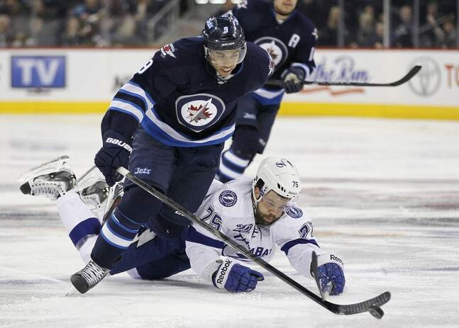 Winnipeg Jets' Evander Kane dodges the check from Tampa Bay Lightning's Radko Gudas during second-period NHL action in Winnipeg on Sunday.