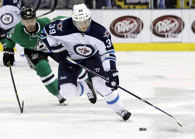 Winnipeg Jets defenceman Tobias Enstrom controls the puck as Dallas Stars forward Vernon Fiddler (gives chase in the first period.