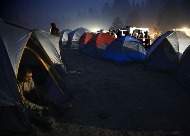 Firefighters wake up at the crack of dawn in a tent camp at the Rim fire base camp near Groveland, Calif., Monday.