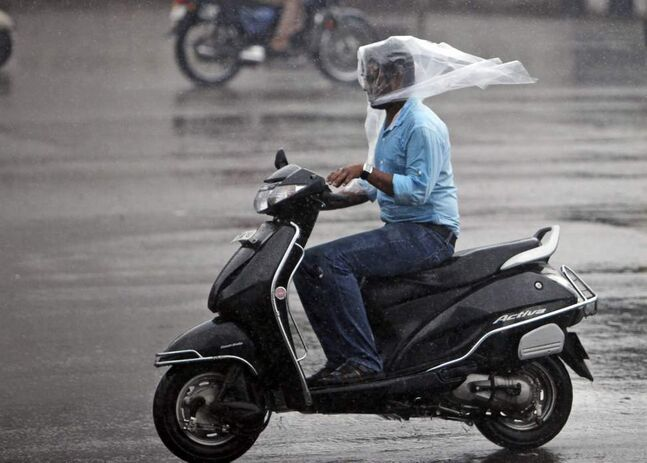 An Indian uses a plastic sheet to cover his head while driving a scooter in the rain in Hyderabad, India, Friday, Nov. 2, 2012. (AP Photo/Mahesh Kumar A.)