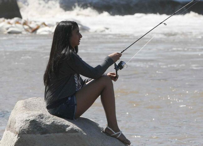 Bilaxshy Sibaturunathan relaxes while fishing on the Red River at Lockport, Man.