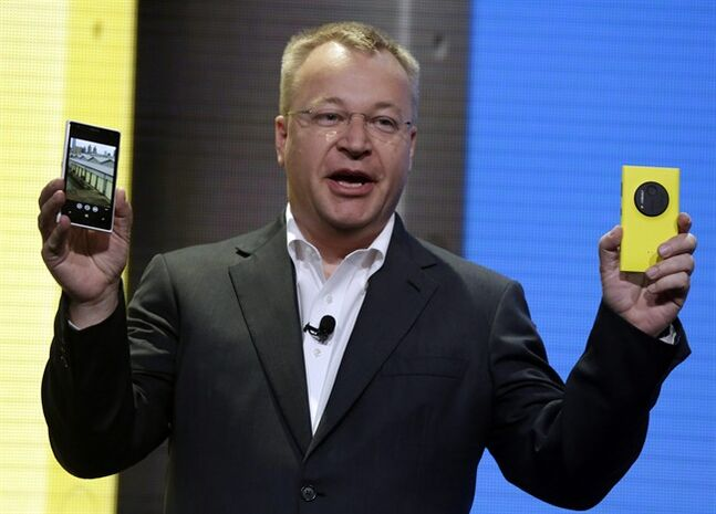 FILE - In this July 11, 2013 file photo, then Nokia CEO Stephen Elop shows the company's Nokia Lumia 1020, in New York. Elop, now Microsoft Executive Vice President, sent employees of the company's devices business a memo detailing its job cut plans. Microsoft on Thursday, July 17, 2014 said it would cut up to 18,000 jobs over the next year, with about 12,500 related to Microsoft's acquisition of Nokia's phone business in April. (AP Photo/Richard Drew, File)
