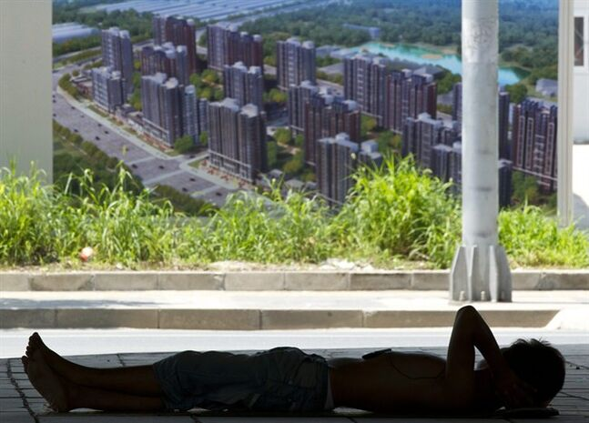 A migrant worker rests in the shade outside a construction site near an advertisement for the real estate project in Beijing Thursday, July 12, 2012. From shopkeepers to shipbuilders, China's deepest slowdown since the 2008 global crisis is inflicting more pain in some areas than still-robust headline growth of about 8 percent might suggest. (AP Photo/Alexander F. Yuan)