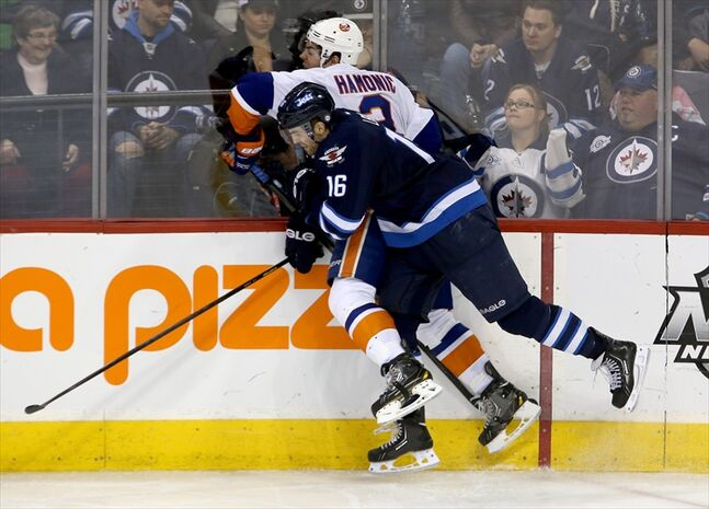 Travis Hamonic is hit hard into the boards by Andrew Ladd during the third period.