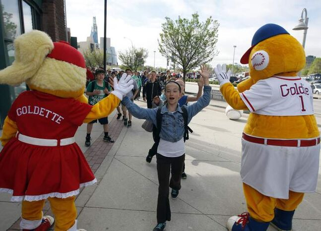 Katrianna Usipiuk, from Edward Schreyer School in Beausejour, is greeted by Goldeyes mascots as students arrive at the Shaw Park. Approximately 3,500 schoolchildren from around the city and province attended the  Goldeyes' afternoon  home game vs. the Laredo Lemurs.