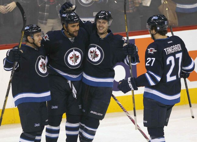 Winnipeg Jets defenceman Dustin Byfuglien (second from left) is congratulated by teammates (from left) Grant Clitsome, James Wright, and Eric Tangradi after a first-period goal that initially given to Byfuglien but later credited to Tangradi.