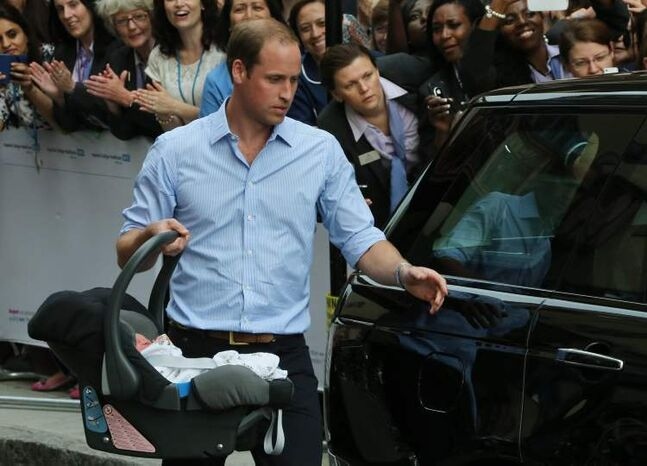Prince William carries the Prince of Cambridge to the car as they leave St. Mary's Hospital's exclusive Lindo Wing in London.