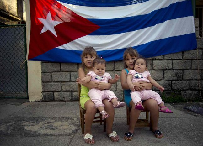 Six-year-old twins Asley and Aslen Velazquez hold eight-month-old twins Tiffani and Stessany Valles as they pose for portraits in front a Cuban flag on their street in Havana, Cuba.