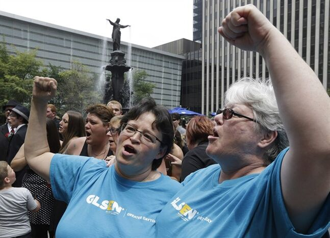Tina Gilley, left, and Skye McKenna cheer after they were united in a commitment ceremony, Wednesday, Aug. 6, 2014, on Fountain Square in Cincinnati. Three judges of the 6th U.S. Circuit Court of Appeals in Cincinnati are set to hear arguments Wednesday in six gay marriage fights from four states, Kentucky, Michigan, Ohio and Tennessee. (AP Photo/Al Behrman)