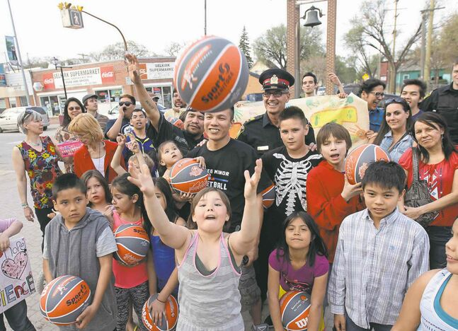 Lenard Monkman, standing behind a ball thrower, is surrounded by kids and community leaders at the Bell Tower on Selkirk Avenue Friday night.