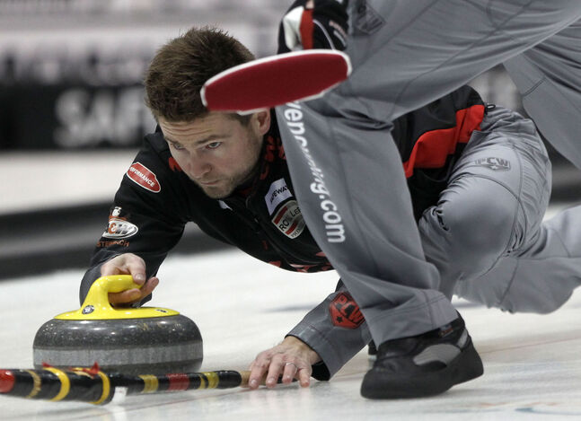 Skip Mike McEwen of the Fort Rouge Curling Club throws during play against  Glenn Parrott of Minnedosa in the first draw of the 2014 Safeway Championships at the MTS Iceplex this morning. McEwen won 10-2 in 8 ends.