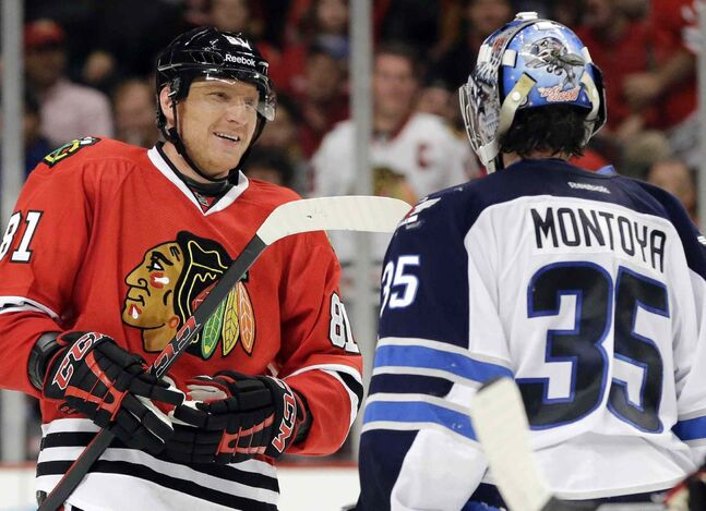 Chicago Blackhawks' Marian Hossa (left) smiles as he talks to Winnipeg Jets goalie Al Montoya during the second period.