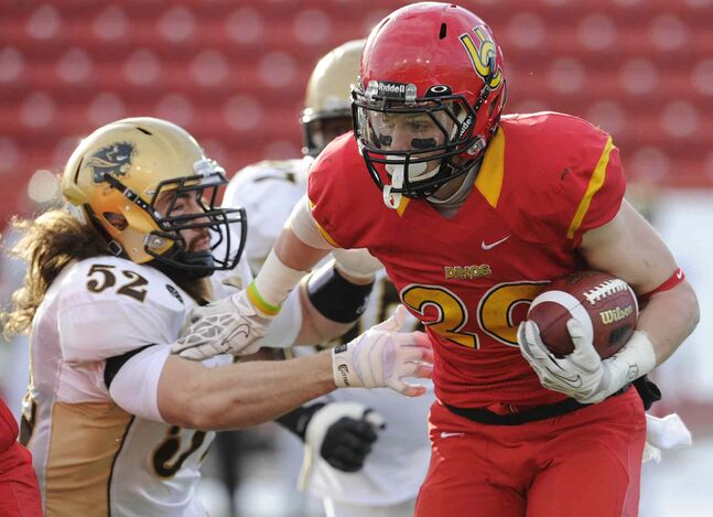 Calgary Dinos' Mercer Timmis (right), breaks free from Thomas Miles of the Bisons during the first half.