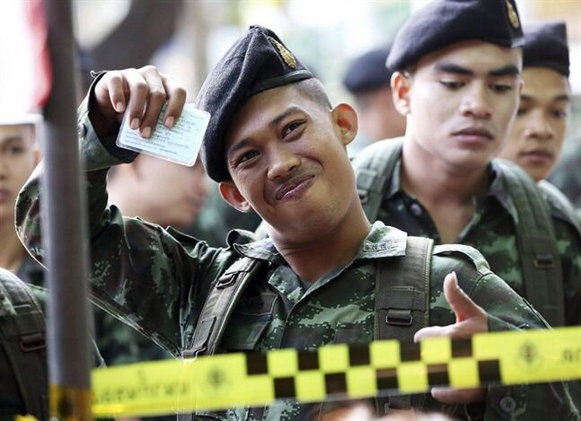 A Thai soldier shows his identity card while waiting in a queue to vote with his colleagues during the general election at a polling station in Bangkok, Thailand Sunday, Feb. 2, 2014. Thailand's tense national election got underway Sunday with protesters forcing the closure of several polling stations in the capital amid fears of more bloodshed a day after gun battles in Bangkok left seven people wounded. (AP Photo/Apichart Weerawong)