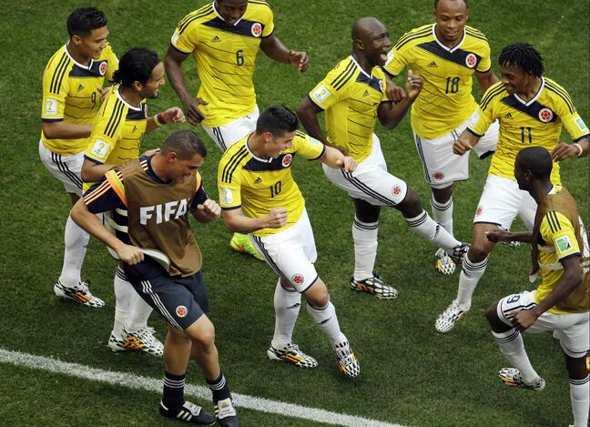 Colombia's James Rodriguez, centre, dances with teammates in celebration after scoring during the group C World Cup soccer match between Colombia and Ivory Coast at the Estadio Nacional in Brasilia, Brazil, June 19.