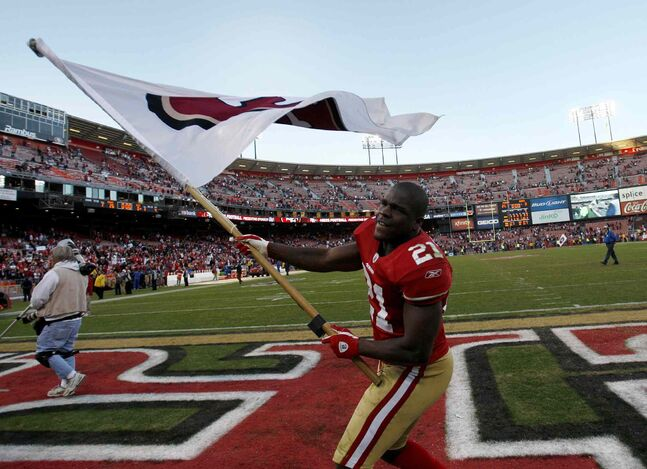 Frank Gore of the San Francisco 49ers waves a 49ers flag after they beat the St. Louis Rams 26-0 at Candlestick Park in December 2011.