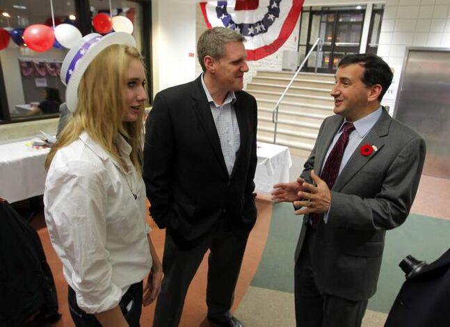 U.S. consul Tim Cipullo, right, holds an election party at the University of Manitoba Tuesday evening. Here, he talks to Natalie Jebb (left) and her father Lee Jebb (centre), both from Brandon.