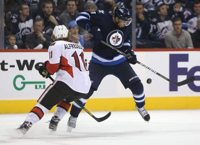 Ottawa Senators' Daniel Alfredsson battles with Winnipeg Jets' Evander Kane for the puck late in the second period of play at MTS Centre Saturday.