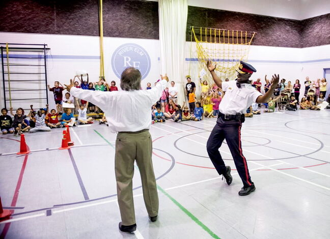 River Elm principal Tom Chan pumps up the crowd with Police Chief Devon Clunis at an event at the school on June 13. Chan played Clunis in a basketball game after students read 2.5 million pages in a 12-month span. Chan has also eaten worms, milked a goat, and danced ballet in a pink tutu in the name of literacy.