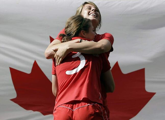 Canada's Emily Zurrer, rear, and Chelsea Stewart, foreground, celebrate winning their women's bronze medal soccer match against France at the 2012 London Summer Olympics, in Coventry. (AP Photo/Hussein Malla)