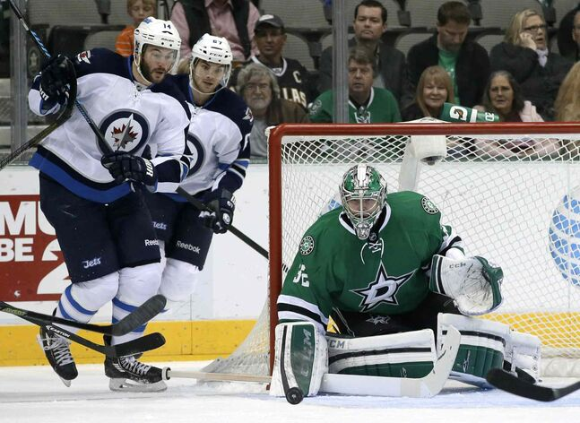 Dallas Stars goalie Kari Lehtonen (right) makes a stop as Winnipeg Jets forwards Anthony Peluso (left) and Michael Frolik track the puck during the first period of Saturday night's game in Dallas.