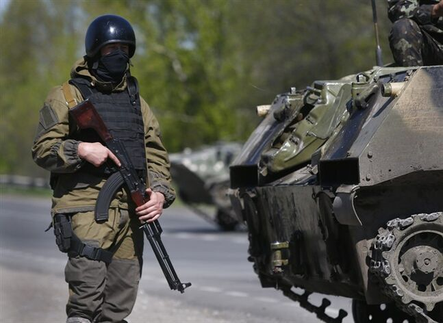 A soldier of the Ukrainian army guards their checkpoint near village of Malinovka, 20 kilometers (12,5 miles) from Slovyansk, eastern Ukraine, Sunday, April 27, 2014. Insurgents in Slovyansk have taken a number of people hostage, including journalists and pro-Ukraine activists, as they strengthen their control in the east of the country in defiance of the interim government in Kiev and its Western supporters. (AP Photo/Sergei Grits)