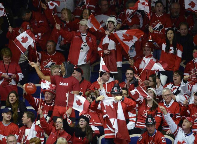 Fans hold up Canadian flags at the IIHF World Junior Hockey Championship game again the United States in Malmo, Sweden on Tuesday, December 31, 2013.