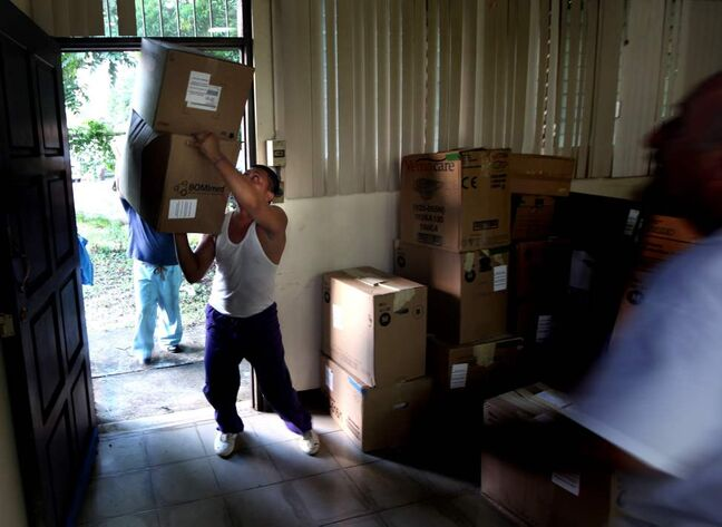A delivery man juggles a stack of boxes as the Op-Walk's medical supplies arrive at the hospital in Managua.