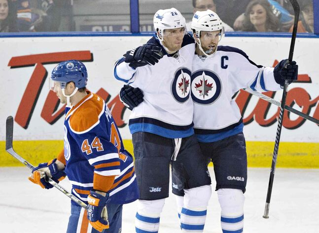 Winnipeg Jets' Blake Wheeler (26) and Andrew Ladd (16) celebrate a goal as Edmonton Oilers' Corey Potter (44) skates past during  the second period Monday.