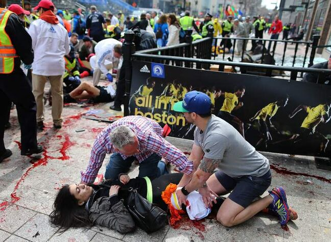 An injured woman is tended to at the finish line of the Boston Marathon, in Boston, Monday, April 15, 2013.