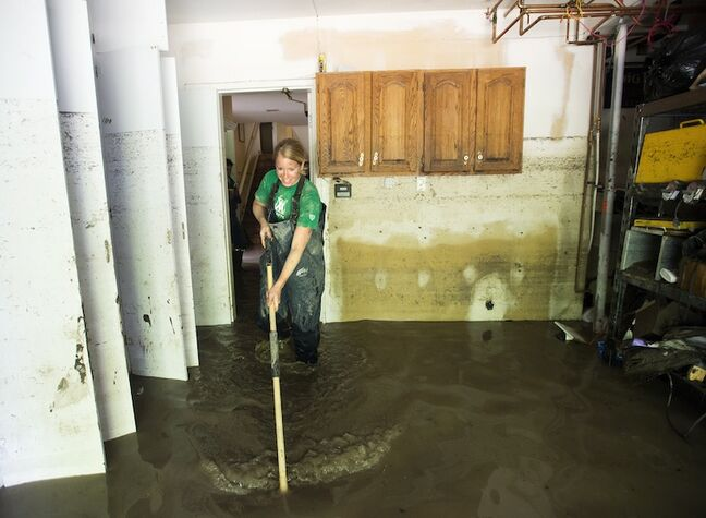 Sarah Watts sports hip-waders as she sweeps water from the house to the garage in the community of Bowness in Calgary Monday.