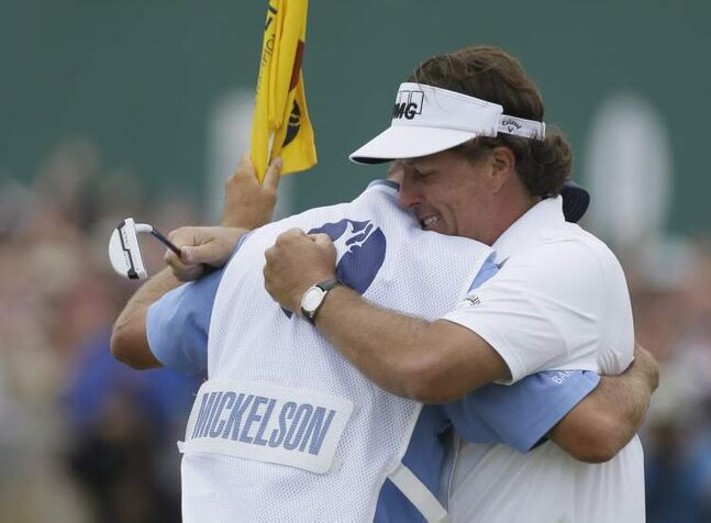 Phil Mickelson closed with an eight-foot birdie putt and then hugged caddie Jim Mackay, whispering 'I did it.'