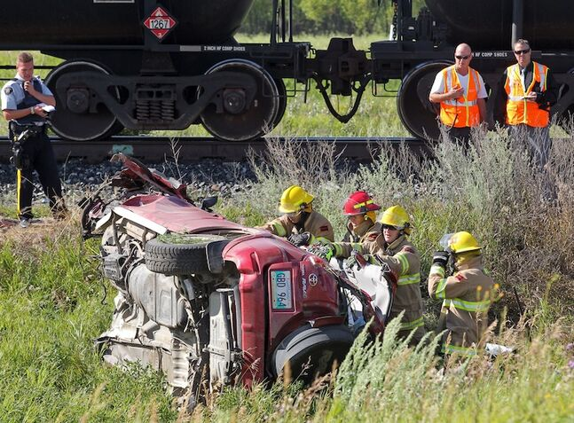 Emergency crews work to free the driver of a Toyota SUV that collided with a train at a railway crossing near Brandon Thursday afternoon. (Colin Corneau/Brandon Sun)