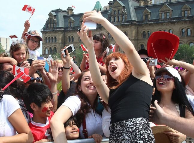 Canadian singing star Carly Rae Jepsen takes a photo with fans after she performed at the Canada Day celebrations on Parliament Hill in Ottawa.