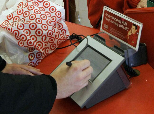 A customer signs his credit card receipt at a Target store in Tallahassee, Fla. The discount retailer confirmed Monday its data-security breach involved malicious software.