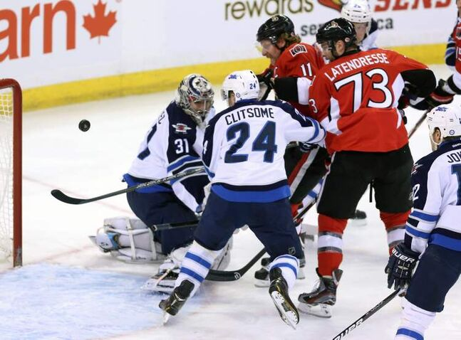 Ottawa Senators' Daniel Alfredsson (11) and Guillaume Latendresse watch as the puck sails past Winnipeg Jets goaltender Ondrej Pavelec and defenceman Grant Clitsome during first-period NHL action in Ottawa Sunday. The Jets were down 2-0 after one period and wound up losing 4-1.