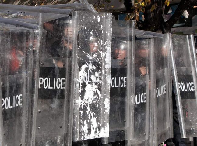 Kosovo police officers take cover behind shields as supporters of the opposition party