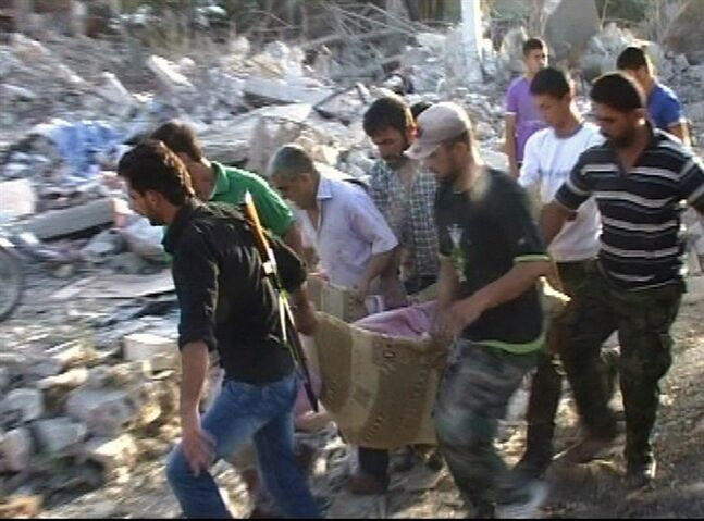 In this photo taken from video released by the Syrian official news agency SANA, Syrians carry a victim from a massive car bomb in the central village of Horrah, in the province of Hama, Syria, Friday, June 20, 2014. A massive car bomb exploded Friday in a government-controlled village in central Syria, dozens of people were killed and wounded, Syrian state media reported. (AP Photo/SANA)