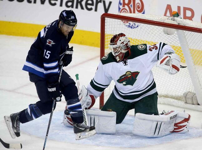 Winnipeg Jets' Matt Halischuk jumps over a shot as he tries to screen Minnesota Wild's goaltender Niklas Backstrom Saturday.