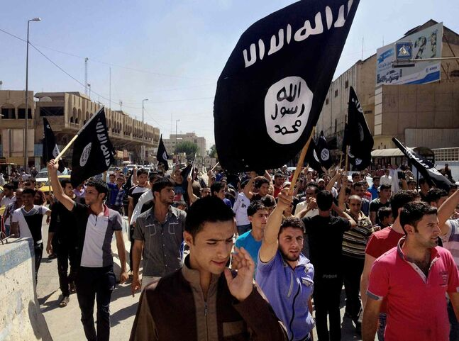 In this June 16, 2014 file photo, demonstrators chant pro-Islamic State group slogans as they carry the group's flags in front of the provincial government headquarters in Mosul, 225 miles (360 kilometers) northwest of Baghdad.