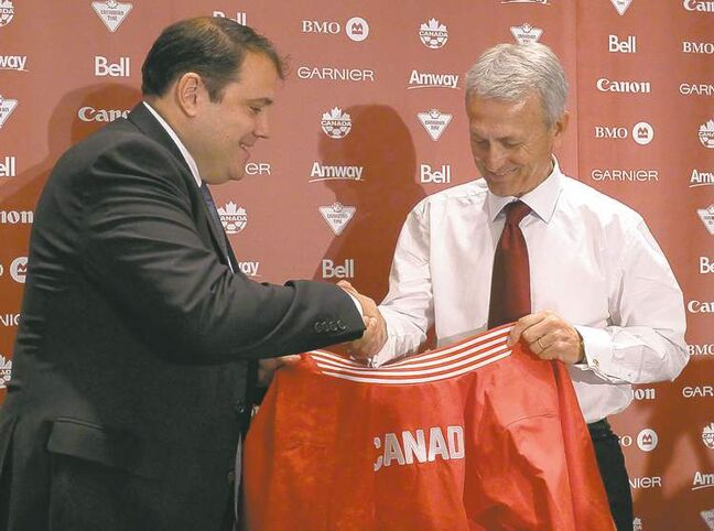 Canadian Soccer Association president Victor Montagliani (left) presents Benito Floro, the Canadian men's national  soccer team's new manager, with an appropriate jacket at the introductory news conference in Toronto Friday.