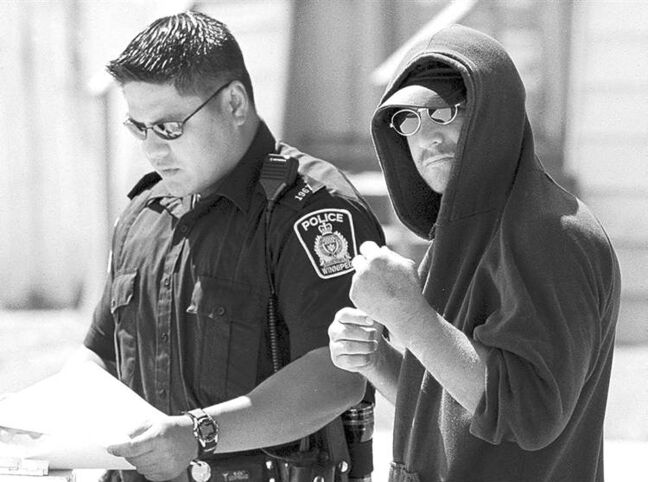 Kevin Sylvester, seen here speaking to police after a 2001 attack on his house, would like to mentor at-risk youth.