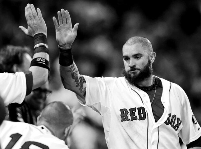 The Boston Red Sox's Jonny Gomes is congratulated after scoring in the fourth inning of Saturday's win over Tampa.
