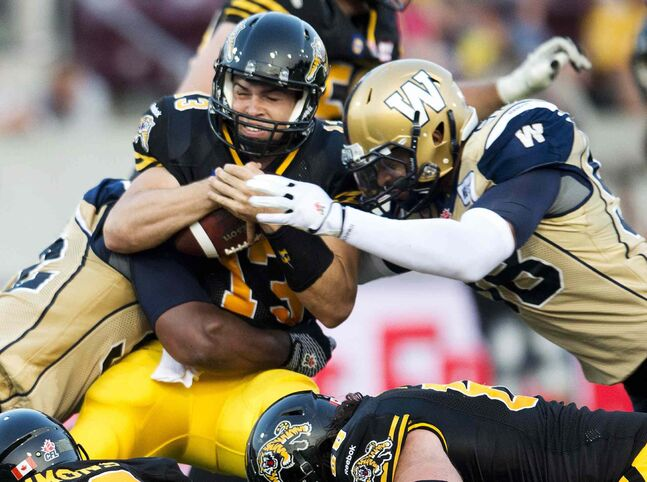 Hamilton Tiger-Cats' quarterback Dan LeFevour, centre, gets sacked by Winnipeg Blue Bombers' defensive end Jason Vega, right, in the first half of CFL football action in Hamilton, Ont., on Thursday.