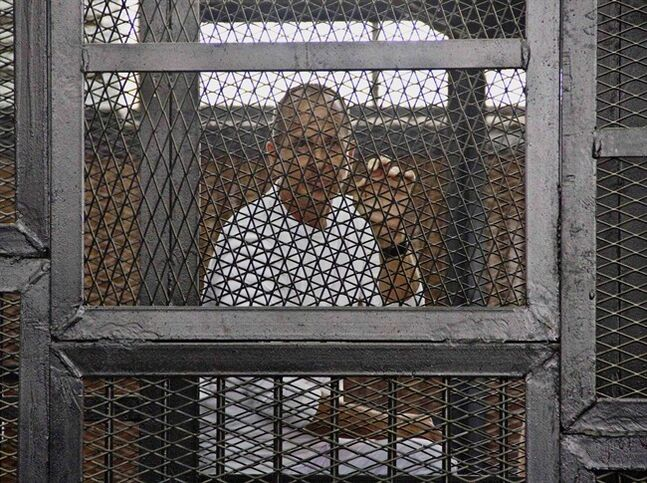 FILE - In this May 3, 2014 file photo, Al-Jazeera's award-winning Australian correspondent Peter Greste appears in a defendants' cage in the Police Academy courthouse along with several other defendants during a trial on terror charges in Cairo, Egypt. Australian Prime Minister Tony Abbott said Monday, June 23 that he told Egyptian President Abdel Fatah al-Sisi that the jailed Australian journalist is innocent of charges that he supported the outlawed Muslim Brotherhood. (AP Photo/Hamada Elrasam, File)