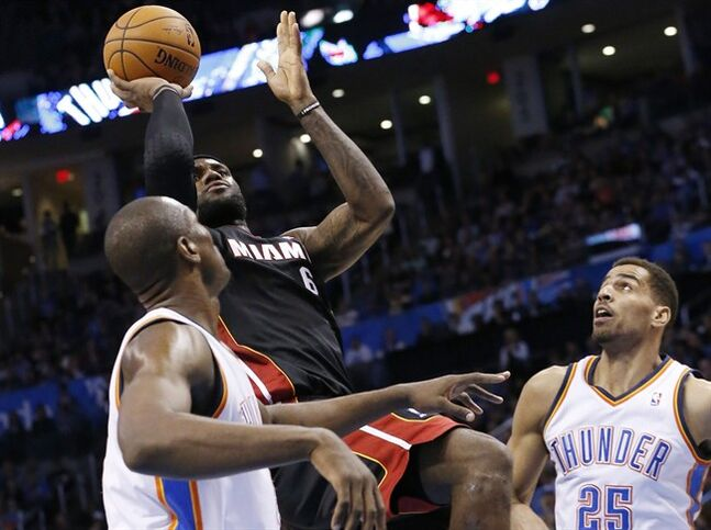Miami Heat forward LeBron James (6) shoots between Oklahoma City Thunder forward Serge Ibaka (9) and guard Thabo Sefolosha (25) during the second quarter of an NBA basketball game in Oklahoma City, Thursday, Feb. 20, 2014. (AP Photo/Sue Ogrocki)