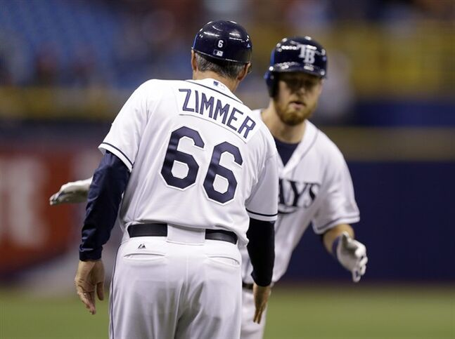 Tampa Bay Rays third base coach Tom Foley, wearing a jersey in honor of senior baseball advisor Don Zimmer, reaches out to shake hands with Ben Zobrist after Zobrist hit a two-run home run off Miami Marlins starting pitcher Tom Koehler during the first inning of an interleague baseball game Wednesday, June 4, 2014, in St. Petersburg, Fla. Foley had been wearing the jersey for a few weeks. (AP Photo/Chris O'Meara)