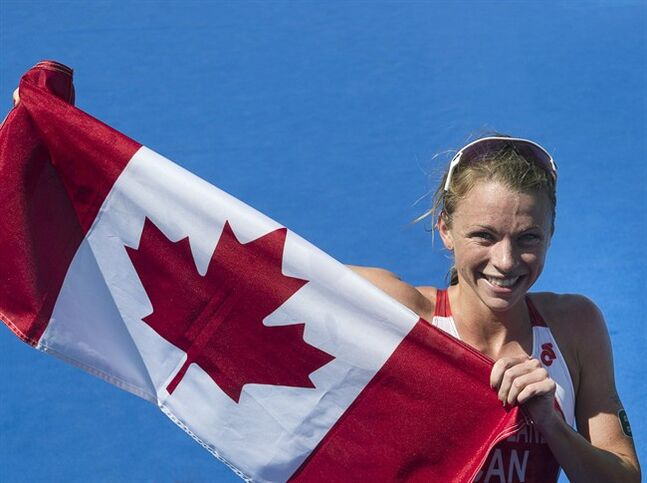 Canada's Kirsten Sweetland from Victoria, B.C., waves to the crowd after winning the silver medal in the women's triathlon at Strathclyde Country Park in Glasgow, Scotland on Thursday, July 24, 2014. The medal is Canada's first of the Games.THE CANADIAN PRESS/Andrew Vaughan