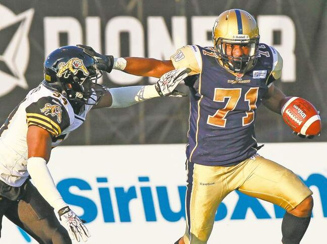 Aaron Lynett / the canadian pressBlue Bombers receiver Trevor Kennedy stiff-arms Hamilton defender Ryan Hinds Thursday night in Guelph.