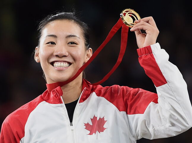 Canada's Michelle Li displays her gold medal after defeating Scotland's Kirsty Gilmour in badminton action at the Commonwealth Games in Glasgow, Scotland Sunday.